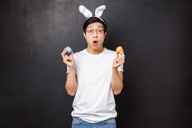 Feiertags-, party- und osterkonzept. erstaunter junger asiatischer mann in hasenohren, der gemalte eier hält, als er freundentraditionen lernt, offener mund fasziniert, neue kultur kennenzulernen,