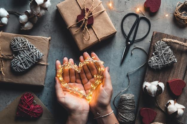 Feiertags-, personen- und feierkonzept - nahaufnahme der frau, die valentinsgeschenke verziert