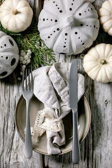 Feiertags-tischdekoration mit weißen dekorativen kürbissen, handgefertigten tonkürbissen, thuja-zweigen, leerem teller mit stoffserviette, besteck über altem holztisch. flach liegen.