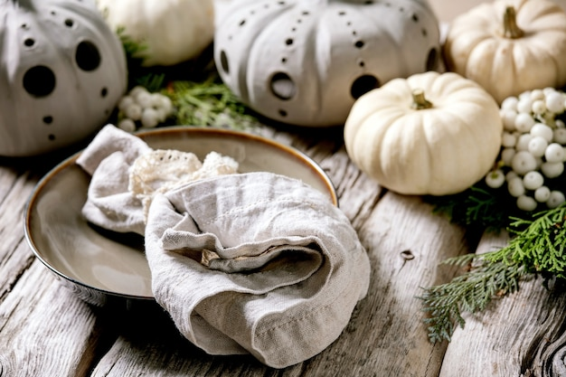 Feiertags-tischdekoration mit weißen dekorativen kürbissen, handgefertigten tonkürbissen, thuja-zweigen, leerem teller mit stoffserviette über altem holztisch. nahansicht