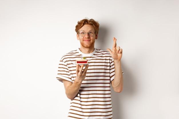 Feiertags- und feierkonzept. fröhlicher rothaariger mann in den gläsern, die geburtstagstorte mit kerze halten, kreuzfinger für viel glück und wunsch machen, weißer hintergrund.