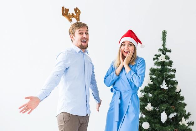 Feiertags- und feierkonzept - junges lustiges paar, das weihnachten zu hause feiert