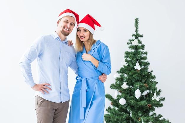 Feiertags- und feierkonzept - junges paar, das weihnachten zu hause feiert