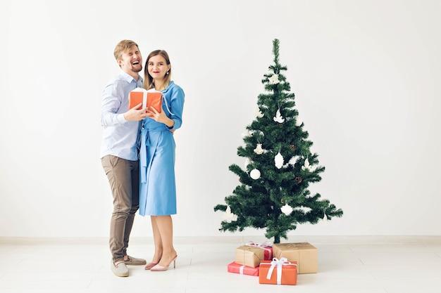Feiertags- und feierkonzept - nettes junges paar, das weihnachtsgeschenke vor einem weihnachtsbaum austauscht