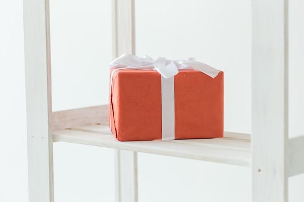 Feiertags- und geburtstagskonzept - rote geschenkbox mit weißem band, das auf dem regal steht.