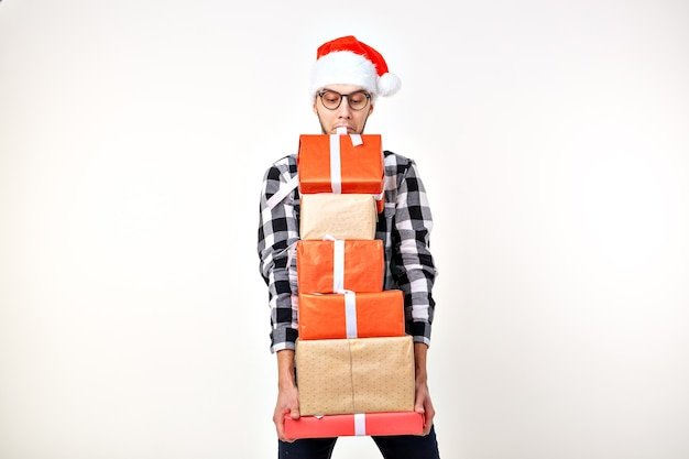 Feiertags- und geschenkkonzept - lustiger mann in weihnachtsmütze, der viele geschenkboxen auf weißem hintergrund mit kopienraum hält