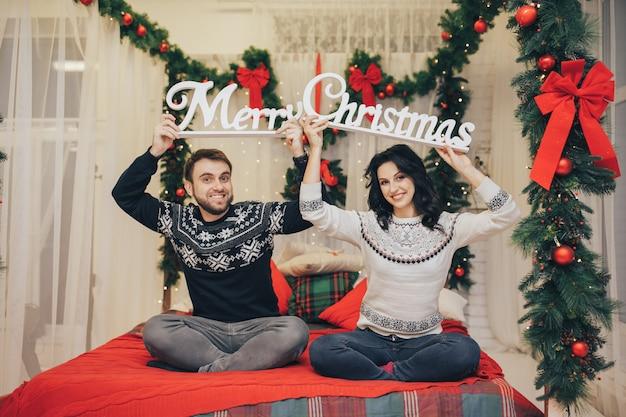 Feiertags- und neujahrskonzept. paar in winterkleidung, die über lichthintergrund umarmt
