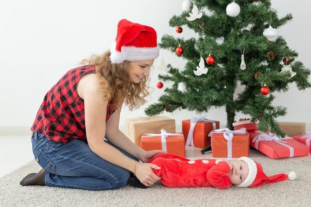 Feiertags- und weihnachtskonzept - junge mutter mit baby-weihnachtsmann vor weihnachtsbaum