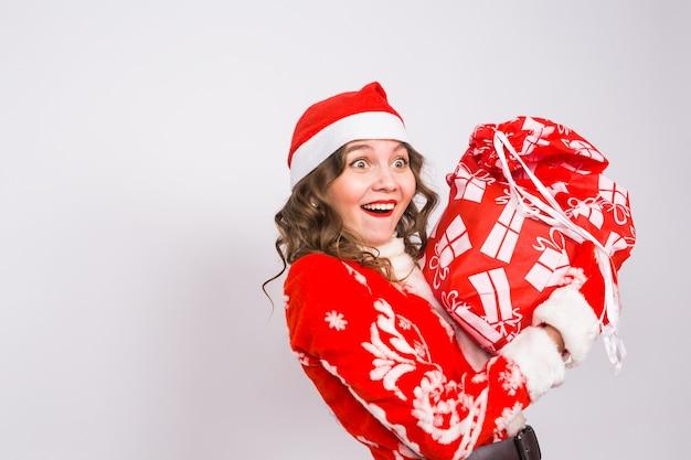 Feiertags-, weihnachts- und personenkonzept - frau mit überraschtem smiley im weihnachtsmannkostüm mit geschenktüte
