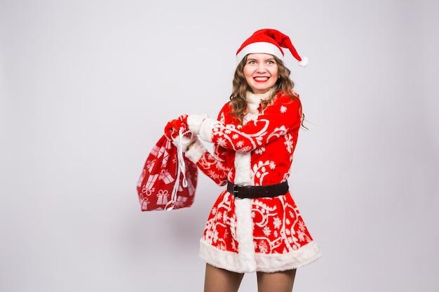 Feiertags-, weihnachts- und personenkonzept - wütende frau im weihnachtsmannkostüm mit geschenktüte.