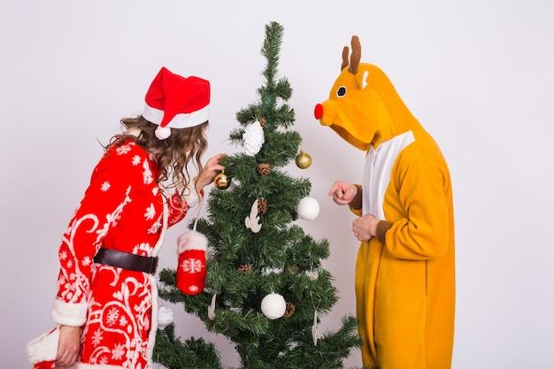 Feiertags-, weihnachts- und spaßkonzept - lustiger mann und frau in den hirsch- und weihnachtsmannkostümen nahe weihnachtsbaum auf weißem hintergrund.