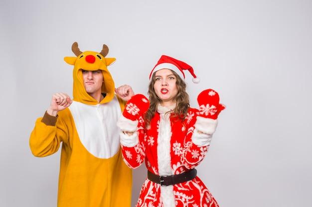 Feiertags-, weihnachts- und spaßkonzept - lustiges paar im hirschkostüm und in der weihnachtsmannkleidung tanzen auf weißer oberfläche