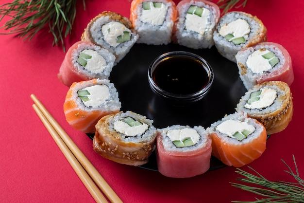 Feiertags-weihnachtsbrunch-sushi-satz von lachs, thunfisch und aal mit philadelphia-käse als kranz auf einem roten hintergrund. nahansicht
