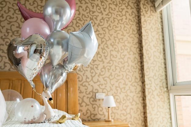 Feiertagsballone und flamingospielzeug auf dem bett