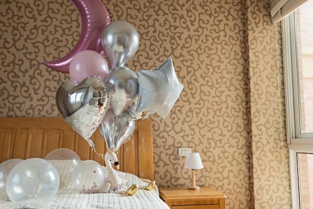 Feiertagsballons und angefülltes flamingospielzeug auf dem bett