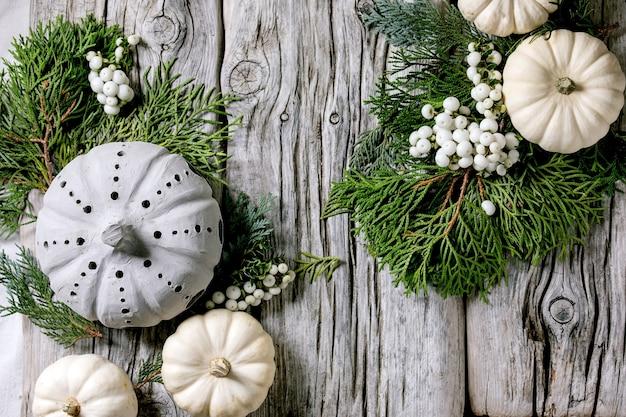 Feiertagsdekoration mit weißen dekorativen kürbissen, handgefertigten tonkürbissen, thujazweigen, beeren über altem holztisch. flach liegen