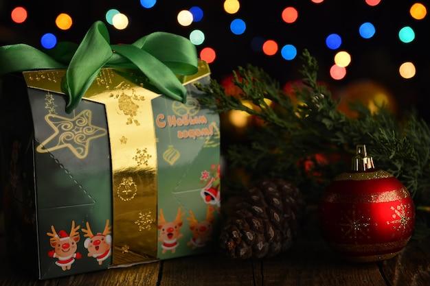 Feiertagsdekorationen weihnachtshintergrundfrohes neues jahr auf geschenk auf russischer sprache