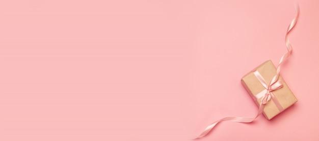 Feiertagsfahne. draufsicht eines geschenks eingewickelt als geschenkkraftpapier verziert mit einem band auf rosa