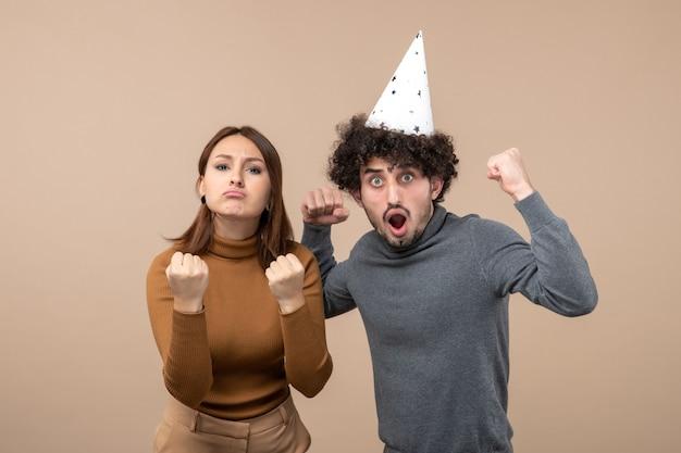 Feiertagsfest- und partykonzept - glückliches emotional aufgeregtes stolzes reizendes junges paar auf grau