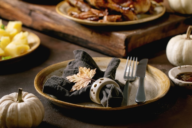 Feiertagsgedeck mit klassischen gerichten geröstete glasierte ente mit äpfeln, salzkartoffeln und soße, leere keramikplatte mit serviette und herbstblatt auf dunklem tisch mit herbstdekor.