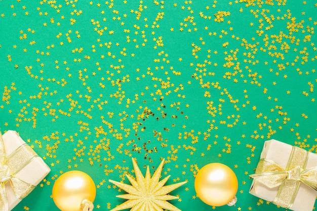 Feiertagshintergrund, goldene weihnachtskugeln und geschenkboxen auf einem grünen hintergrund mit glitzernden goldenen sternen, flache lage, draufsicht