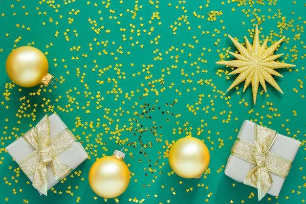 Feiertagshintergrund, goldene weihnachtskugeln und geschenkboxen auf grünem hintergrund mit goldenen glitzersternen, flache lage, draufsicht