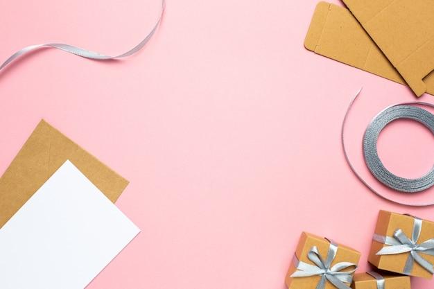 Feiertagshintergrund mit geschenk in der kastenzusammensetzung und -band auf rosa papier