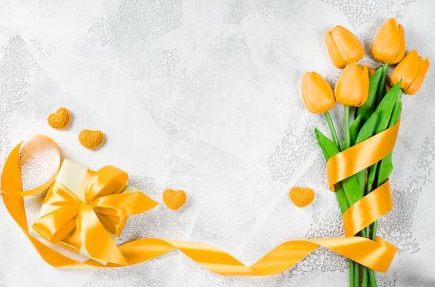 Feiertagshintergrund mit tulpen und geschenkbox