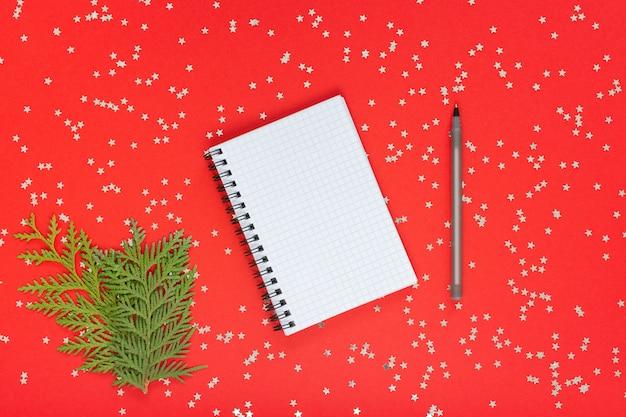 Feiertagshintergrund, offener spiralblock und stift- und thujazweige auf einem roten
