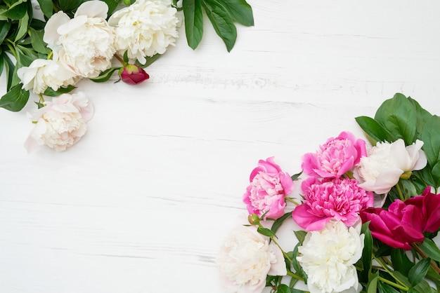 Feiertagshintergrund. rosa und weißer pfingstrosenrahmen auf weißem hölzernem hintergrund. textfreiraum, ansicht von oben.