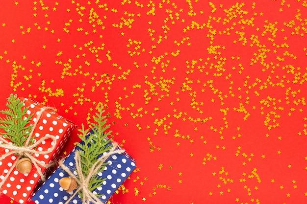 Feiertagshintergrund, rote und blaue geschenkboxen in tupfen mit band und schleife und thuja-zweigen auf rotem hintergrund mit glitzernden goldenen sternen, flache lage, draufsicht