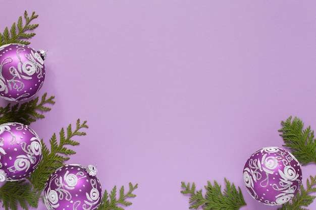 Feiertagshintergrund, weihnachtskugeln und thujazweige auf einem lila hintergrund, flache lage, draufsicht