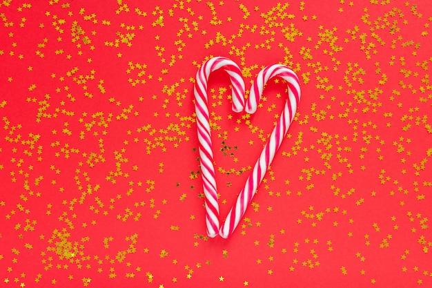 Feiertagshintergrund, weihnachtszuckerstange in form eines herzens auf einem roten hintergrund mit glitzernden goldenen sternen