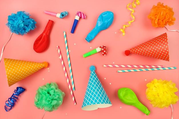 Feiertagshüte, pfeifen, ballons auf rosa hintergrund. konzept der kindergeburtstagsfeier.
