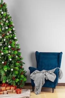 Feiertagsinnenraum. schöner verzierter weihnachtsbaum mit blauem lehnsessel