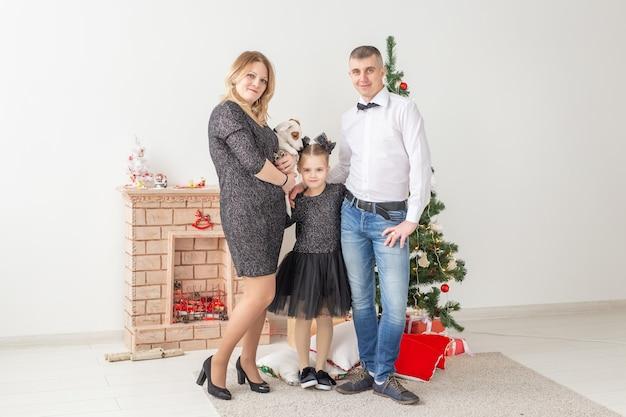 Feiertagskonzept - glückliche familie, mutter, vater und kind am weihnachtsbaum zu hause.