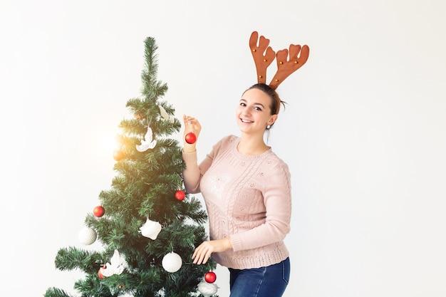 Feiertagskonzept - lustige junge frau verzierte weihnachtsbaum auf weißem hintergrund mit kopienraum. warten auf weihnachten.
