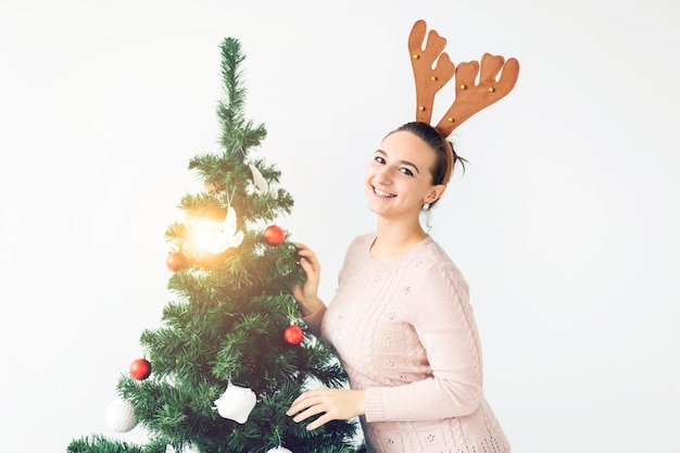 Feiertagskonzept - lustige junge frau verzierte weihnachtsbaum auf weißem hintergrund. warten auf weihnachten.