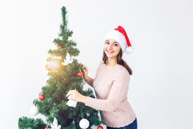 Feiertagskonzept - mädchen im sankt-hut verzierten weihnachtsbaum. warten auf weihnachten.