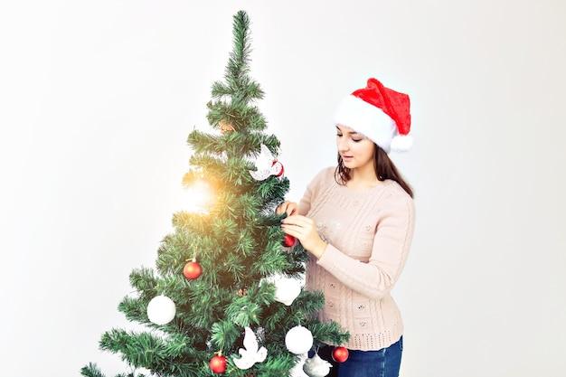 Feiertagskonzept - mädchen im sankt-hut verzierten weihnachtsbaum. warten auf weihnachten. Premium Fotos