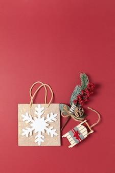 Feiertagspaket mit weißer schneeflocke, blumenstrauß mit dem gezierten zweig und beeren, spielzeugschlitten auf rot.