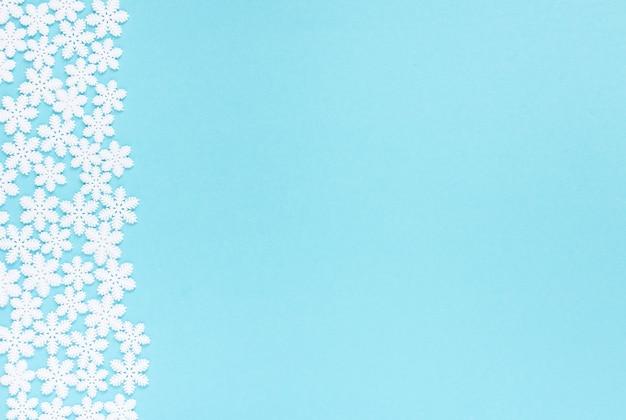 Feiertagspastellhintergrund, weiße schneeflocken auf einem sanften blauen hintergrund, flache lage, draufsicht