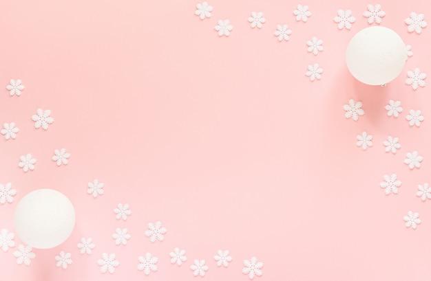 Feiertagspastellhintergrund, weiße schneeflocken und weihnachtskugel auf einem sanften rosa hintergrund, flache lage, draufsicht