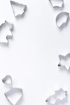 Feiertagsrahmen aus metall-ausstechformen für hausgemachtes weihnachtlich gebackenes gebäck auf weiß