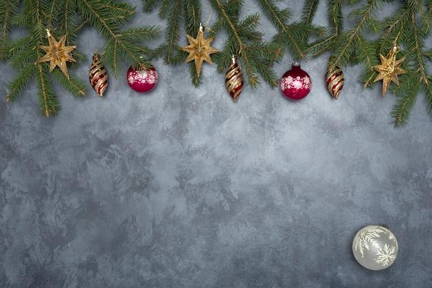 Feiertagsrahmen von weihnachtsdekorationen auf konkretem hintergrund des blauen dunklen stucks mit tannenzweig
