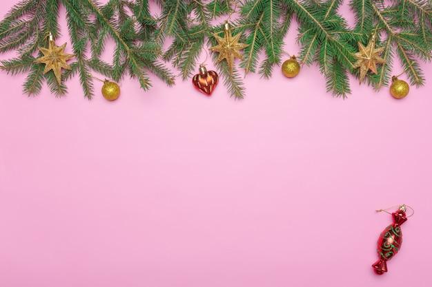 Feiertagsrahmen von weihnachtsdekorationen auf rosa hintergrund mit tannenzweig