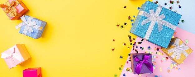 Feiertagsrahmenkomposition mit geschenken und dekoration auf gelber oberfläche mit kopierraum für text