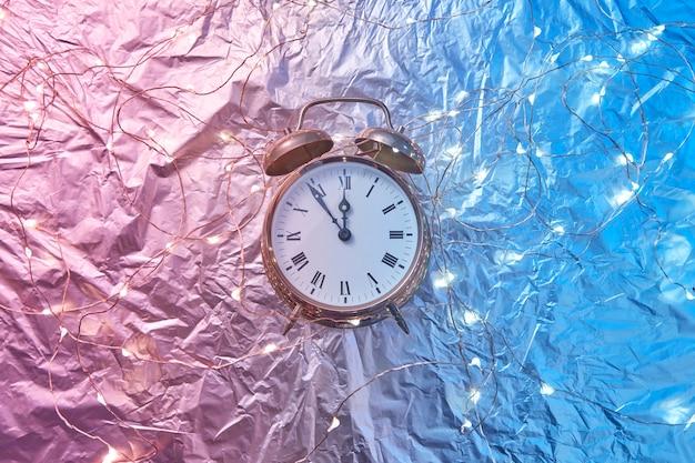 Feiertagsschnur der lichter und des alten weckers auf einem duotone rosa blauen goldenen hintergrund mit kopienraum. die weihnachtszeit ist zwischen fünf minuten und mitternacht.