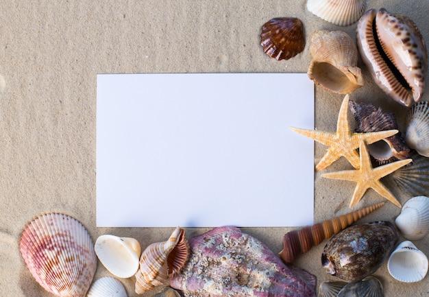 Feiertagsstrandkonzept mit oberteilen, seesternen und einer leeren postkarte
