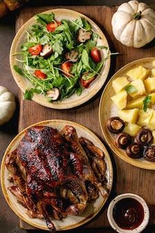 Feiertagstisch mit klassischen gerichten gebratene glasierte ente mit äpfeln, salzkartoffeln, grünem salat und sauce auf dunklem holztisch mit herbstdekor. flach legen